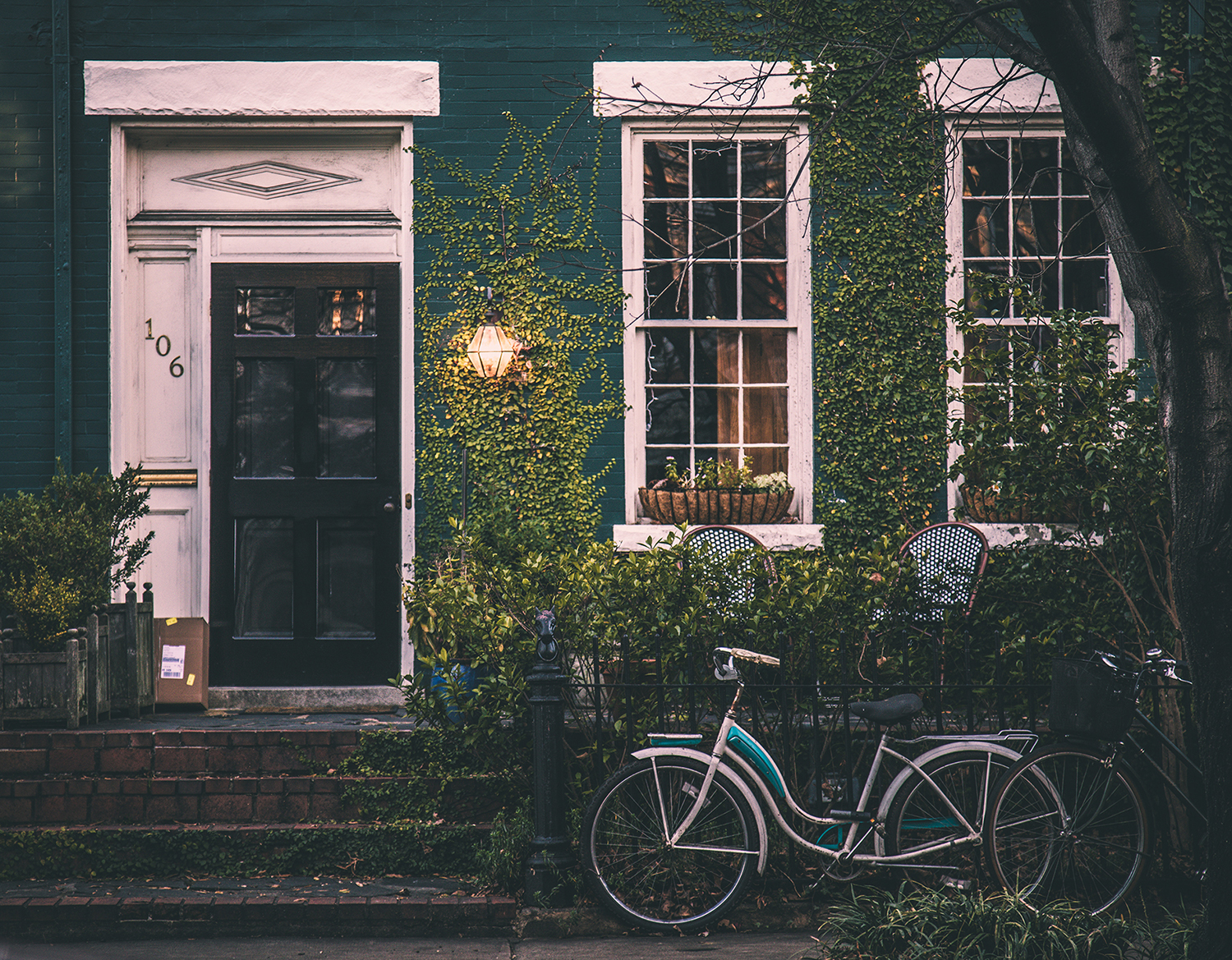 Photo of green brick home with bicycle